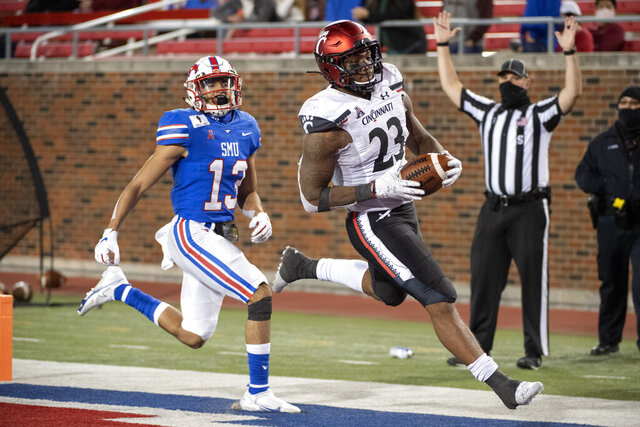 Cincinnati running back Gerrid Doaks (23) cruises into the end zone in front of SMU safety Roderick Roberson, Jr. (13) on a touchdown run during the second half of an NCAA college football game Saturday, Oct. 24, 2020, in Dallas. Cincinnati won 42-13. (AP Photo/Jeffrey McWhorter)
