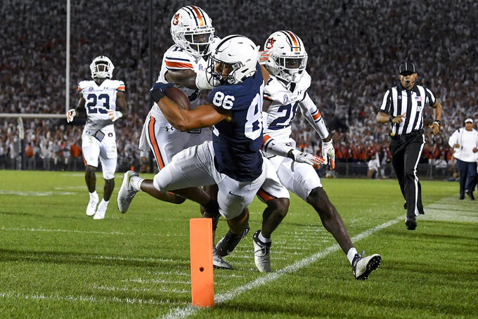 Penn State tight end Brenton Strange (86) dives toward the end zone while being tackled by Auburn safety Zion Puckett (11) and safety Smoke Monday, right, the fourth quarter of an NCAA college football game in State College, Pa., Saturday, Sept. 18, 2021. Penn State won 28-20. (AP Photo/Barry Reeger)