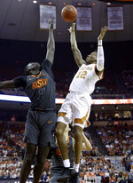 Texas guard Kerwin Roach II (12) shoots over Oklahoma State forward Yor Anei (14) during the second half of an NCAA college basketball game, Saturday, Feb. 16, 2019, in Austin, Texas. Texas won 69-57. (AP Photo/Eric Gay)