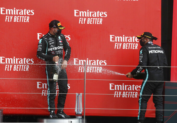 Second place Mercedes driver Lewis Hamilton of Britain, right, sprays champagne on third place, Mercedes driver Valtteri Bottas of Finland, after the 70th Anniversary Formula One Grand Prix at the Silverstone circuit, Silverstone, England, Sunday, Aug. 9, 2020. (AP Photo/Frank Augstein, Pool)