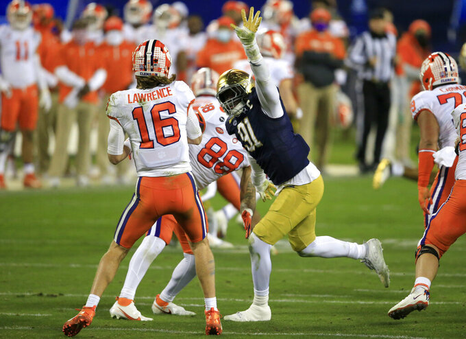 Notre Dame defensive lineman Adetokunbo Ogundeji (91) pressures Clemson quarterback Trevor Lawrence (16) during the second half of the Atlantic Coast Conference championship NCAA college football game, Saturday, Dec. 19, 2020, in Charlotte, N.C. (AP Photo/Brian Blanco)