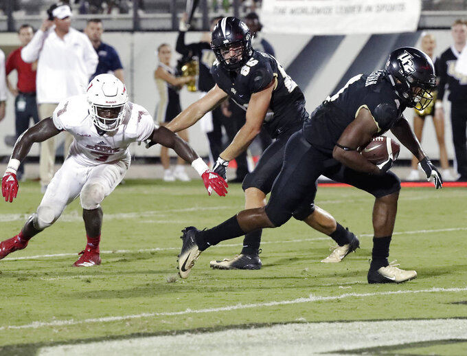 Central Florida running back Taj McGowan, right, runs for a 6-yard touchdown as tight end Michael Colubiale, center, blocks Florida Atlantic cornerback Shelton Lewis (3) during the second half of an NCAA college football game, Friday, Sept. 21, 2018, in Orlando, Fla. (AP Photo/John Raoux)