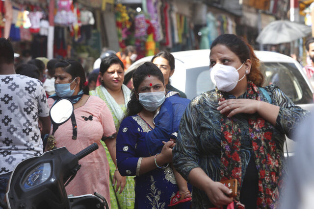 Indians wearing face masks as a precaution against the coronavirus walk in a market in Jammu, India, Friday, Oct. 9, 2020. India is the world's second most coronavirus affected country after the United States. (AP Photo/Channi Anand)