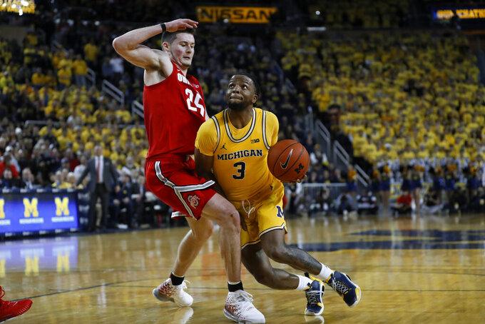 Michigan guard Zavier Simpson (3) drives on Ohio State forward Kyle Young (25) in the second half of an NCAA college basketball game in Ann Arbor, Mich., Tuesday, Feb. 4, 2020. (AP Photo/Paul Sancya)