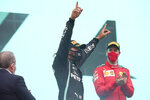 Third placed Ferrari driver Sebastian Vettel of Germany, right, applauds as Mercedes driver Lewis Hamilton of Britain celebrates after winning the Formula One Turkish Grand Prix at the Istanbul Park circuit racetrack in Istanbul, Sunday, Nov. 15, 2020. (Tolga Bozoglu/Pool via AP)