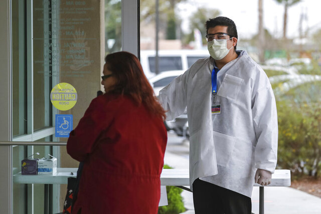 Frank Tzontlimatzi holds the door open for patients while wearing gloves and a mask at La Clinica de Familia in Las Cruces, N.M. on Wednesday, March 18, 2020. New Mexico confirmed Wednesday a coronavirus infection that has no apparent link to travel as the governor takes new steps to limit the spread of the contagion by limiting restaurants to take-out service and closing down movie theaters, gyms and shopping centers. (Nathan J. Fish/The Las Cruces Sun News via AP)