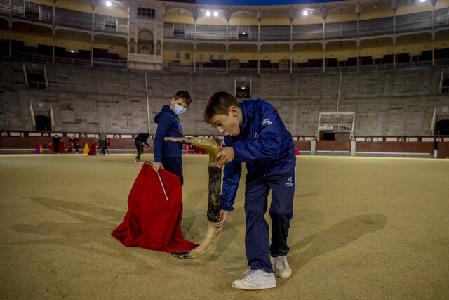 Pupils Nicolas Sanz Luna, 10, right, performs holding a plastic bull horns with Daniel at the Bullfighting School at Las Ventas bullring in Madrid, Spain, Tuesday, Dec. 22, 2020. They are students of the Bullfighting School at Las Ventas bullring in Madrid, where children as young as 9 can begin learning this deadly dance of human and beast so closely associated with Spanish identity. The school was closed from March to August when Spain went into one of the world's strictest confinements to stem the spread of the COVID-19 pandemic.(AP Photo/Manu Fernandez)