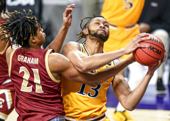 Drexel forward Tim Perry Jr. (13) and Elon forward Michael Graham (21) vie for a rebound during the first half of an NCAA college basketball game for the Colonial Athletic Association men's tournament championship in Harrisonburg, Va., Tuesday, March 9, 2021. (AP Photo/Daniel Lin)
