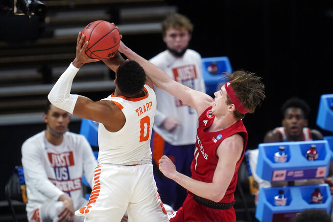 Rutgers guard Paul Mulcahy, right, defends Clemson guard Clyde Trapp (0) during the second half of a men's college basketball game in the first round of the NCAA tournament at Bankers Life Fieldhouse in Indianapolis, Friday, March 19, 2021. (AP Photo/Paul Sancya)