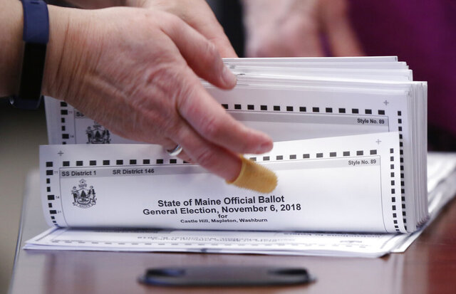 FILE – In this Nov. 12, 2018 file photo, ballots are prepared to be tabulated in Maine's 2nd Congressional District election in Augusta, Maine. A state supreme court decision Tuesday, Spet. 8, 2020, cleared the way for election officials to print ranked choice voting ballots for the first time in Maine's presidential election. But there has not been a final ruling on whether the voting system will be used in that contest. (Robert F. Bukaty/File)