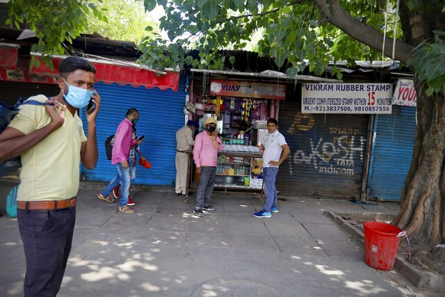 Indians stand outside a local snack shop during extended lockdown in New Delhi, India, Monday, May 18, 2020. India has recorded its biggest single-day surge in new cases of coronavirus. The surge in infections comes a day after the federal government extended a nationwide lockdown to May 31 but eased some restrictions to restore economic activity and gave states more control in deciding the nature of the lockdown. (AP Photo/Manish Swarup)