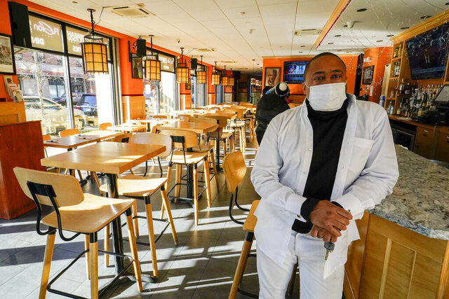 Andrew Walcott, owners of Fusion East Caribbean & Soul Food restaurant, poses for a photo at the restaurant in East New York neighborhood of the Brooklyn borough of New York, Thursday, Jan. 7, 2021.  Walcott had to furlough four employees at his restaurant just before Christmas, after New York state stopped allowing indoor dining.   (AP Photo/Mary Altaffer)