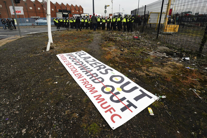 A protest banner lies left on the ground with police officers in the background, as Manchester United fans demonstrate against the Glazer family, the American owners of Manchester United, before their English Premier League soccer match against Liverpool at Old Trafford stadium in Manchester, England, Thursday, May 13, 2021. (AP Photo/Jon Super)