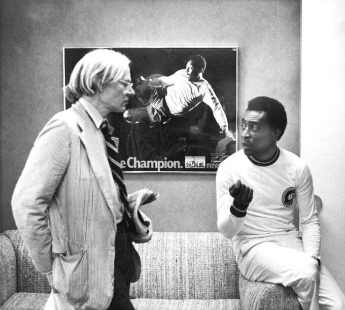 FILE - In this  July 26, 1977 file photo, surrealist artist Andy Warhol speaks with Brazil's soccer player Pele about a portrait after Warhol was commissioned to make a series of portraits of athletic stars in New York. On Oct. 23, 2020, the three-time World Cup winner Pelé turns 80 without a proper celebration amid the COVID-19 pandemic as he quarantines in his mansion in the beachfront city of Guarujá, where he has lived since the start of the pandemic. (AP Photo/Claudia Larson, File)