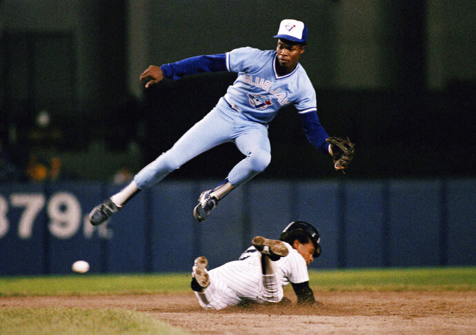 FILE - In this Sept. 18, 1987, file photo, New York Yankees' Rickey Henderson, bottom, steals second base below Toronto Blue Jays shortstop Tony Fernández during a baseball game in New York.  Fernández, a stylish shortstop who made five All-Star teams during his 17 seasons in the major leagues and helped the Blue Jays win the 1993 World Series, died Sunday, Feb. 16, 2020, after complications from a kidney disease. He was 57. (AP Photo/G. Paul Burnett, File)