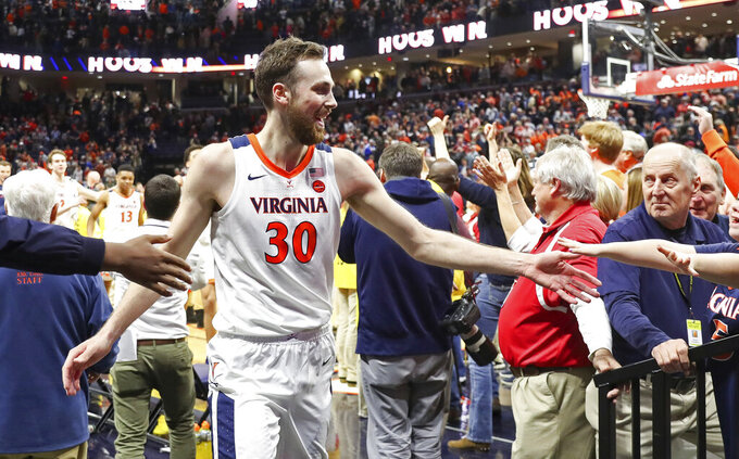 Virginia forward Jay Huff (30) celebrates with fans after defeating Duke in an NCAA college basketball game Saturday, Feb. 29, 2020, in Charlottesville, Va. (AP Photo/Andrew Shurtleff)