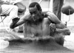 FILE - In this Oct. 18, 1968, file photo, Bob Beamon of El Paso, Texas, digs his feet into the sand pit after a record-shattering long jump of 8.90 meters on his first attempt at the Summer Olympic Games in Mexico City. (AP Photo/File)