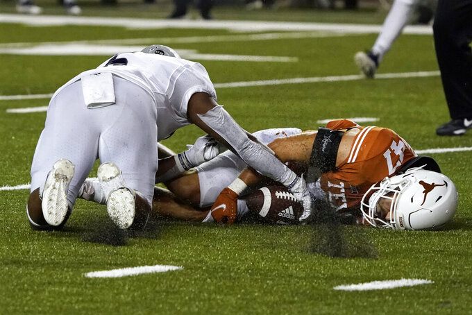 Texas linebacker Luke Brockermeyer (47) and Rice running back Khalan Griffin (6) battle for the ball after Griffin fumbled during the first half of an NCAA college football game on Saturday, Sept. 18, 2021, in Austin, Texas. Texas recovered the ball. (AP Photo/Chuck Burton)