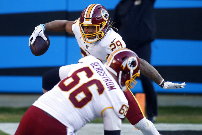 Washington Redskins running back Derrius Guice (29) reacts with center Tony Bergstrom (66) following a long gain by Guice during the second half of an NFL football game against the Carolina Panthers in Charlotte, N.C., Sunday, Dec. 1, 2019. (AP Photo/Brian Blanco)