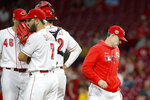 Cincinnati Reds manager David Bell, right, walks off the mound after handing the ball to relief pitcher Kevin Gausman (46) during the ninth inning of the team's baseball game against the Milwaukee Brewers, Tuesday, Sept. 24, 2019, in Cincinnati. (AP Photo/John Minchillo)