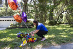 """REMOVES """"UNARMED"""" AND ADDS THAT AUTHORITIES HAVE NOT CONFIRMED THAT ARBERY WAS EITHER ARMED OR UNARMED -  Erica Smith, of Brunswick, Ga., leaves a small paper sign on a memorial at the spot where Ahmaud Arbery was shot and killed Friday, May 8, 2020, in Brunswick Ga. Two men have been charged with murder in the February shooting death of Arbery,a black man in his mid-20s, whom they had pursued in a truck after spotting him running in their neighborhood. (AP Photo/John Bazemore)"""