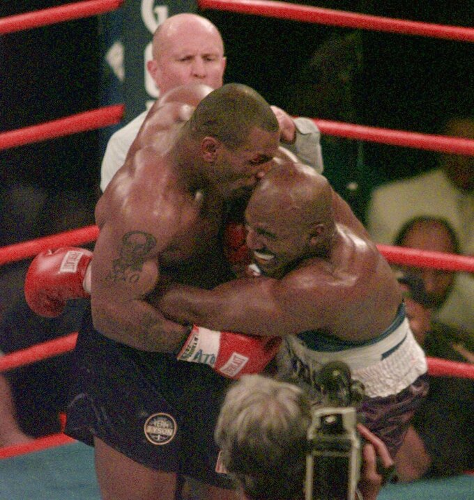 FILE - This June 28, 1997, file photo shows Mike Tyson biting into the ear of Evander Holyfield in the third round of their WBA heavyweight match in Las Vegas. Violence is part of the game in many sports. But when the Cleveland's Myles Garrett ripped the helmet off Mason Rudolph and hit the Pittsburgh Steelers' quarterback in the head with it, the Browns' defender crossed a line _ one that attracts the attention of authorities sometimes from within their sport and in other cases from criminal prosecutors.(AP Photo/Jack Smith, File)