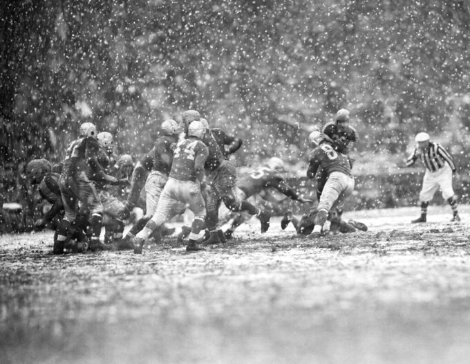FILE - In this Nov. 4, 1945, file photo, Johnny Grigas, right, Boston Yanks is stopped for no gain, when Jack Matheson, (82) Detroit Lions tackled him at Fenway Park in Boston. The Detroit lions defeated the Boston Yanks 10-9 during a heavy snow storm. (AP Photo/File)
