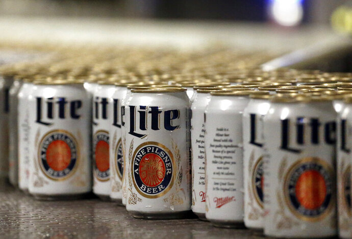 "FILE - In this March 11, 2015 file photo, newly-filled and sealed cans of Miller Lite beer move along on a conveyor belt, at the MillerCoors Brewery, in Golden, Colo. A federal judge has ordered Anheuser-Busch to stop using packaging that implies MillerCoors' light beers contain corn syrup. U.S. District Judge William Conley granted a preliminary injunction sought by MillerCoors. Bud Light's packaging says ""No Corn Syrup"" in bold letters. (AP Photo/Brennan Linsley, File)"