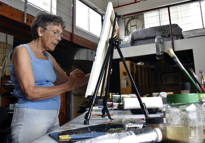 Whitney Peckman works on an oil painting in her art studio, which is right below one of the sleeping spaces in the downtown loft that Peckman and her husband offer on Airbnb, Thursday, June 10, 2021 in Salisbury, N.C.  (Ben Stansell/The Salisbury Post via AP)