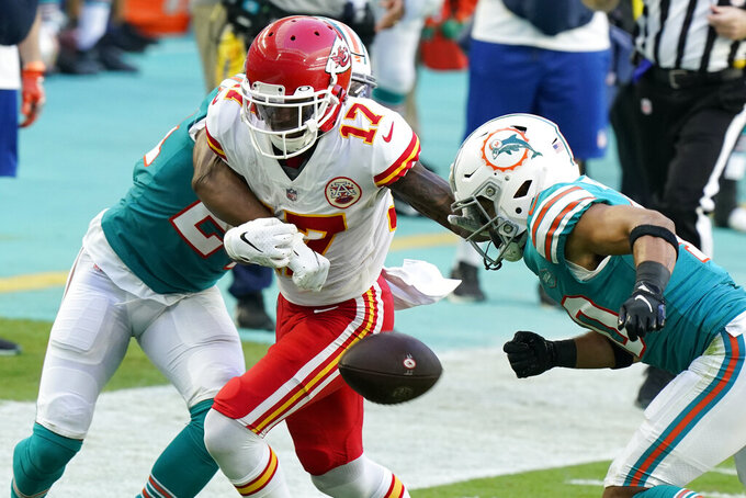 Kansas City Chiefs wide receiver Mecole Hardman (17) fumbles the ball under pressure from Miami Dolphins cornerback Byron Jones (24), left, and defensive back Nik Needham (40), during the second half of an NFL football game, Sunday, Dec. 13, 2020, in Miami Gardens, Fla. (AP Photo/Wilfredo Lee)