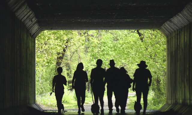 Walkers are silhouetted on the Greenway Trail in Saybrook Township, Ohio, on Saturday May 16, 2020, morning. (Associated Press   Star Beacon, Warren Dillaway)/The Star-Beacon via AP)