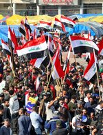Hundreds of people march inside Tahrir Square carrying national flags and chanting religious slogans in Baghdad, Iraq, Thursday, Dec. 5, 2019. Anti-government protesters at least 15 people have suffered stab wounds in Baghdad's Tahrir Square, the epicenter of their movement, after political parties and Iran-backed militia groups briefly joined them, raising fears of infiltration by authorities. (AP Photo/Hadi Mizban)