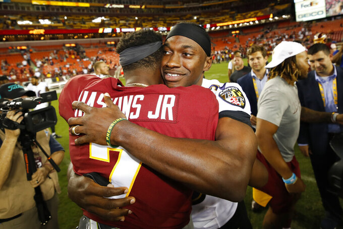 Washington Redskins quarterback Dwayne Haskins (7) and Baltimore Ravens quarterback Robert Griffin III (3) embrace after an NFL preseason football game Thursday, Aug. 29, 2019, in Landover, Md. (AP Photo/Alex Brandon)