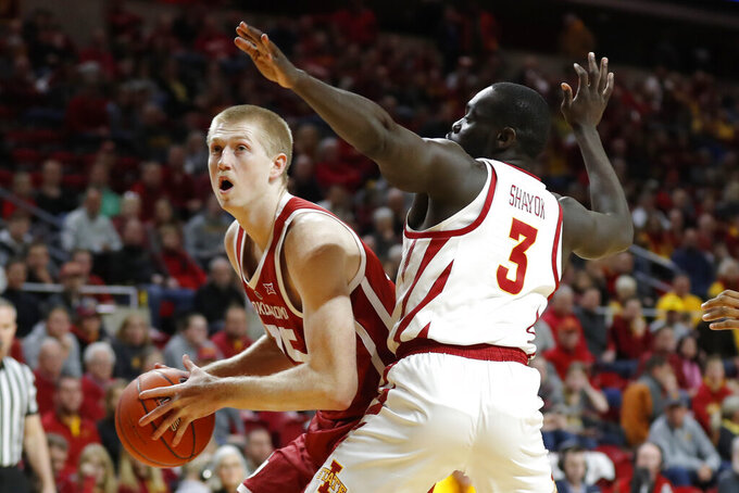 Oklahoma forward Brady Manek drives past Iowa State guard Marial Shayok, right, during the first half of an NCAA college basketball game, Monday, Feb. 25, 2019, in Ames, Iowa. (AP Photo/Charlie Neibergall)