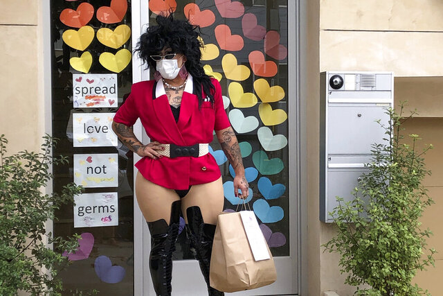 This Friday, Aug. 28, 2020, photo shows Kochina Rude delivering food for customers in San Francisco. A San Francisco drag show night club has taken the show on the road after having to close its doors due to the coronavirus pandemic. Oasis'