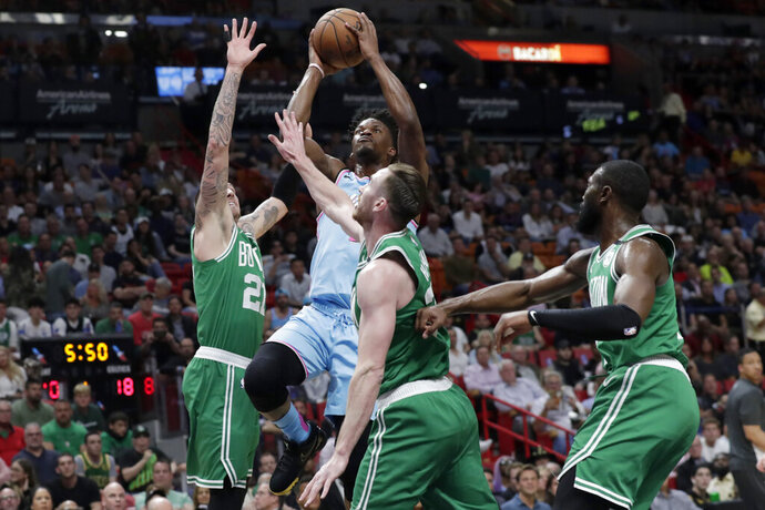 Miami Heat forward Jimmy Butler shoots as Boston Celtics center Daniel Theis (27), forward Gordon Hayward, center, and guard Jaylen Brown, right, defend during the first half of an NBA basketball game, Tuesday, Jan. 28, 2020, in Miami. (AP Photo/Lynne Sladky)