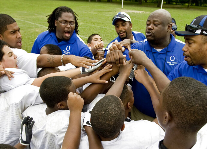 In this image provided by USA Football and taken June 29, 2009, a youth football team comes together at a practice in Dallas. USA Football has developed a phased approach for the return of youth football this year. The plan is based on phased reopening guidelines from the CDC. The governing body for the sport in this country advises youth leagues to consult their city or county health department to determine which CDC phase their community is in. That step begins a youth program's local reopening procedure during the coronavirus pandemic. (USA Football via AP)