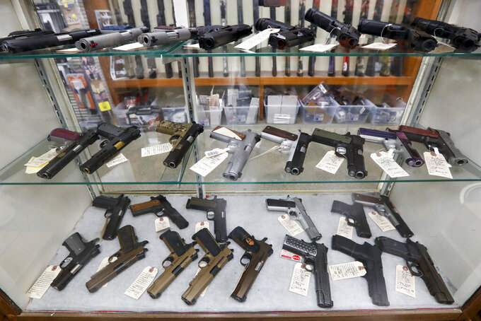 FILE - In this March 25, 2020, file photo semi-automatic handguns are displayed at shop in New Castle, Pa. The number of people stopped from buying guns though the U.S. background check system hit an all-time high of more than 300,000 last year amid a surge of firearm sales, according to new records obtained by the group Everytown for Gun Safety.  The FBI numbers provided to The Associated Press show the background checks blocked nearly twice as many gun sales in 2020 as in the year before.  (AP Photo/Keith Srakocic, File)