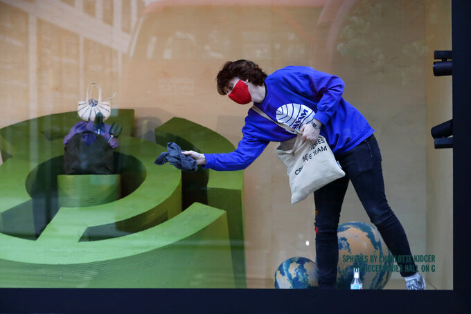 A worker cleans a Selfridges department store shop window on Oxford Street in London, Monday, April 12, 2021. Millions of people in England will get their first chance in months for haircuts, casual shopping and restaurant meals on Monday, as the government takes the next step on its lockdown-lifting road map. (AP Photo/Kirsty Wigglesworth)