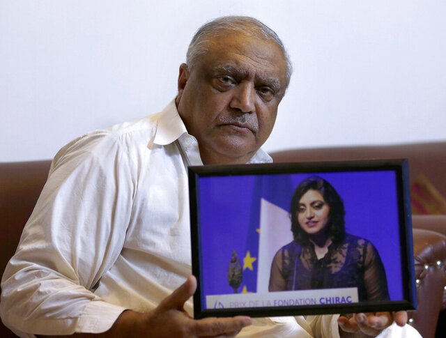 FILE - In this Oct. 17, 2019, file photo, Professor Mohammad Ismail, father of Pakistani human rights activist Gulalai Ismail, holds a photo of his daughter in Islamabad, Pakistan. Ismail, an elderly human rights worker said Friday, Oct. 2, 2020 that his wife and their daughter, who has already fled to America after being targeted by the country's powerful military for investigations into rights abuses by solders, faces a fresh wave of terrorism related charges. (AP Photo/Anjum Naveed, File)