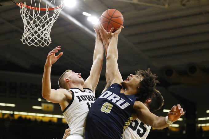 Iowa guard Joe Wieskamp, left, fights for a rebound with Oral Roberts forward Kevin Obanor (0) during the second half of an NCAA college basketball game, Friday, Nov. 15, 2019, in Iowa City, Iowa. (AP Photo/Charlie Neibergall)