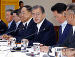 FILE - In this Wednesday, July 10, 2019, file photo, South Korean President Moon Jae-in, third from right, speaks during a meeting with business leaders at the presidential Blue House in Seoul, South Korea. Moon criticized comments by Japanese officials who questioned the credibility of Seoul's sanctions against North Korea while justifying Tokyo's move to strengthen controls on high-tech exports to South Korea. Moon said his government was committed to resolving the matter diplomatically and urged Japan to refrain from pushing the situation to a