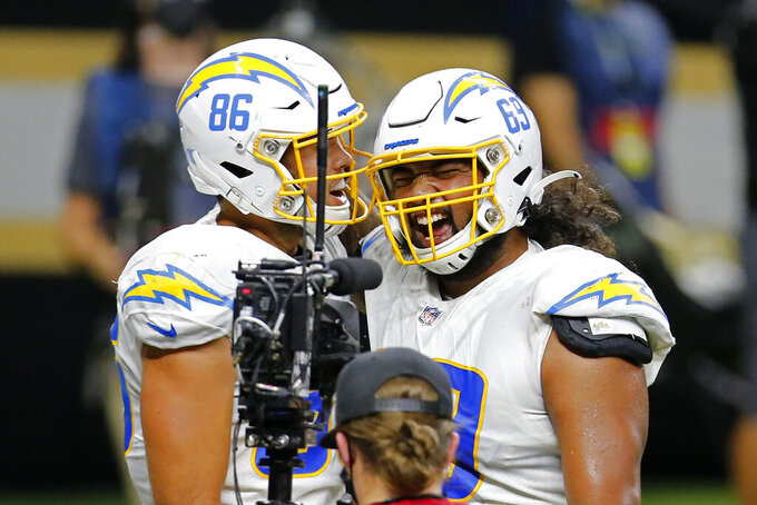 Los Angeles Chargers tight end Hunter Henry (86) celebrates his touchdown reception with offensive tackle Sam Tevi (69) in the first half of an NFL football game against the New Orleans Saints in New Orleans, Monday, Oct. 12, 2020. (AP Photo/Brett Duke)