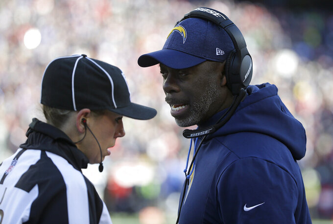 Los Angeles Chargers head coach Anthony Lynn, right, speaks to down judge Sarah Thomas during the first half of an NFL divisional playoff football game against the New England Patriots, Sunday, Jan. 13, 2019, in Foxborough, Mass. Thomas is the first woman to officiate an NFL playoff game. (AP Photo/Steven Senne)
