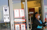 A customer exits a store with a mask required sign displayed, Tuesday, March 2, 2021, in Dallas. (AP Photo/LM Otero)