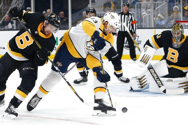 Nashville Predators' Nick Bonino (13) tries to get a shot off as Boston Bruins' Matt Grzelcyk (48) defends during the first period of an NHL hockey game in Boston, Saturday, Dec. 21, 2019. (AP Photo/Michael Dwyer)