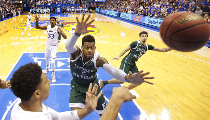 Kansas' Devon Dotson, left, passes the ball under pressure from Eastern Michigan's James Thompson IV (2) during the first half of an NCAA college basketball game Saturday, Dec. 29, 2018, in Lawrence, Kan. (AP Photo/Charlie Riedel)