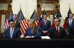 With state Rep. Chris Paddie, left, and state Sen. Kelly Hancock, right, looking on, Texas Gov. Greg Abbott, center, signs two energy related bills, Tuesday, June 8, 2021, in Austin, Texas. Abbot signed legislation into law to reform the Electric Reliability Council of Texas (ERCOT) and weatherize and improve the reliability of the state's power grid. (AP Photo/Eric Gay)