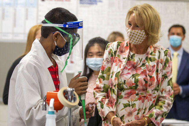 Secretary of Education Betsy DeVo, right, interacts with sophomore Yugeshwar Muralidhar during a visit to a Biotech classroom at Forsyth Central High School in Cumming, Ga., Tuesday, Aug. 25, 2020. (Alyssa Pointer/Atlanta Journal-Constitution via AP)