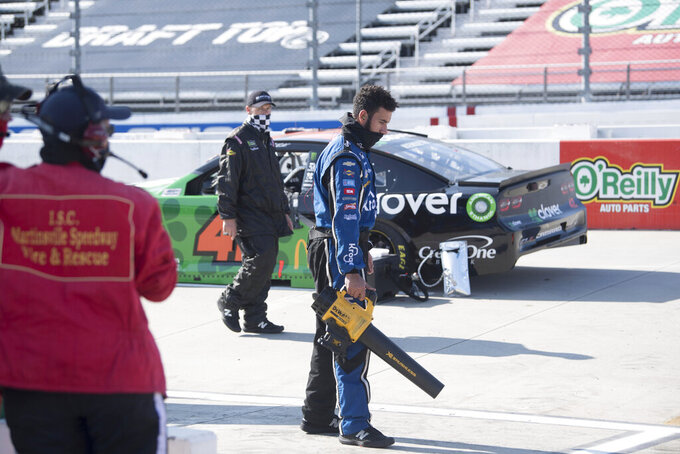 A crew member uses a leaf blower to clean pit area before a NASCAR Cup Series auto race at the Martinsville Speedway in Martinsville, Va., Sunday, Nov.1, 2020. (AP Photo/Lee Luther Jr.)
